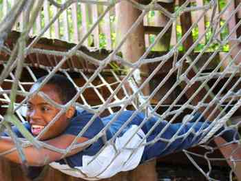 Teenager in hammock in adventure playground at The Limes